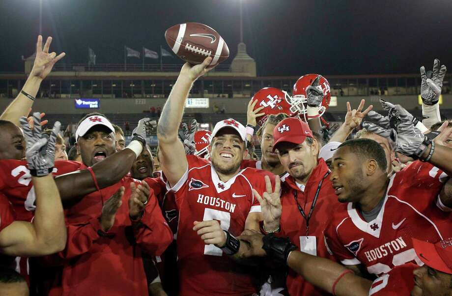 Case Keenum (center) celebrates with his UH teammates after a monster Bayou Bucket game in 2011 at Robertson Stadium.  Photo: Melissa Phillip, Staff / © 2011 Houston Chronicle