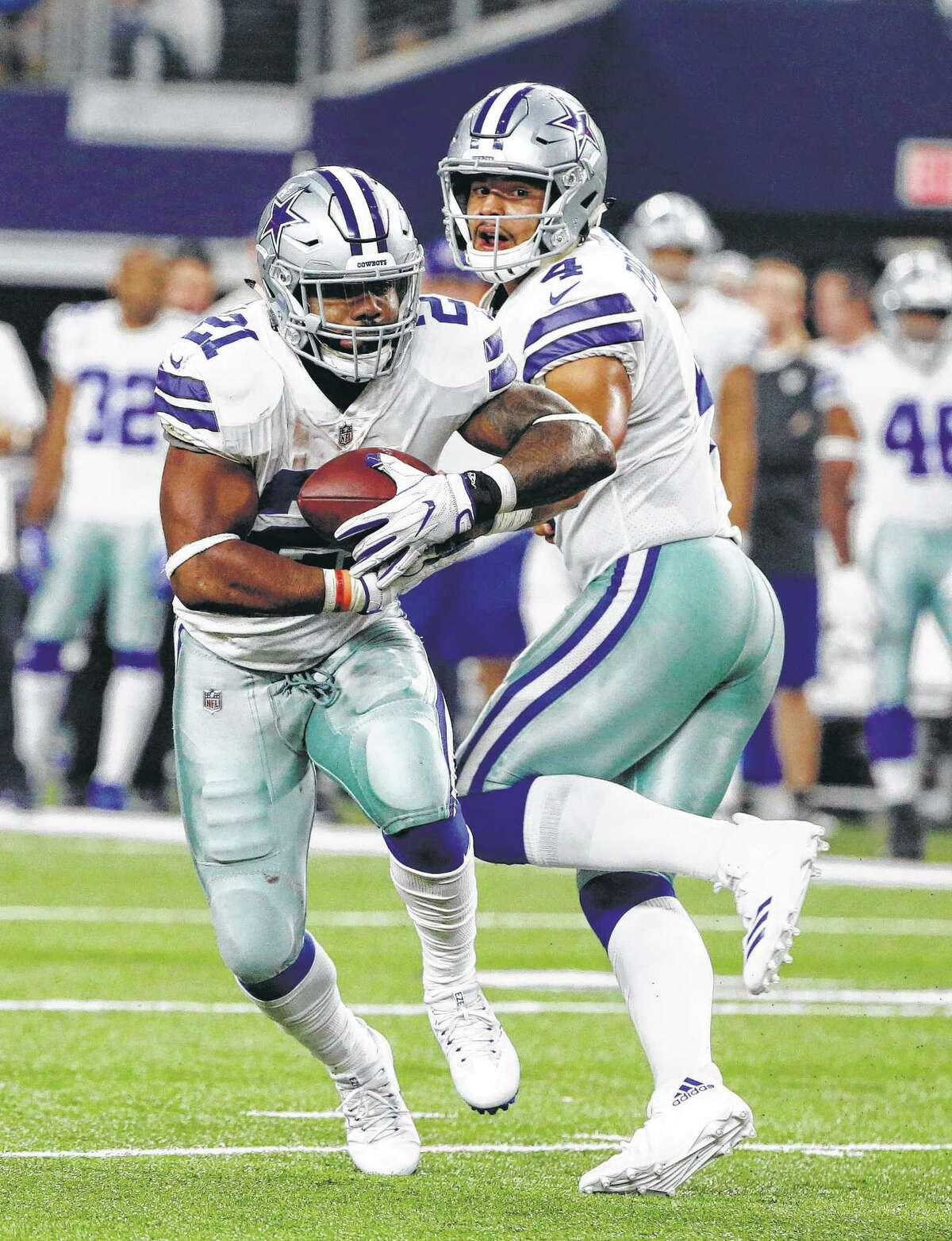 Dallas Cowboys running back Ezekiel Elliott (21) takes the hand off from quarterback Dak Prescott (4) in the first half of an NFL football game against the New York Giants on Sunday, Sept. 10, 2017, in Arlington, Texas. (AP Photo/Michael Ainsworth)