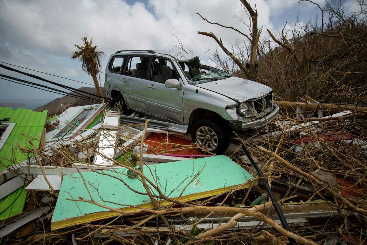 A damaged sports utility vehicle (SUV) sits on top of debris from the destroyed Chateau Bordeaux restaurant after Hurricane Irma at Coral Bay in St John, U.S. Virgin Islands, on Tuesday, Sept. 12, 2017. After being struck by Irma last week, the U.S. Virgin Islands couldn't look less like a tourist destination. Many local residents are giving up and getting out after losing everything to the category 5 storm, even as the local authorities in the U.S. territory say they are determined to rebuild the islands. Photographer: Michael Nagle/Bloomberg ORG XMIT: 775043389