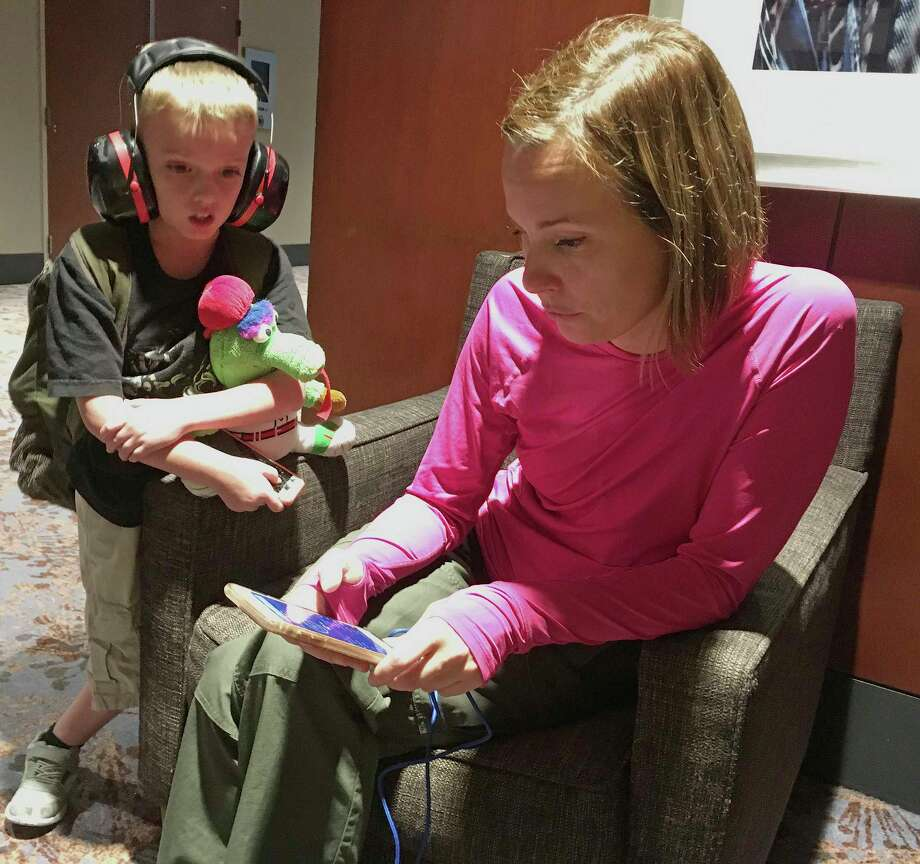 Pam Szymanski of Fort Myers, Fla. and her 8-year-old son Charlie Dutill watch weather radar on Monday, Sept. 11, 2017, as the remnants of Irma move toward metro Atlanta, where their family evacuated to a downtown hotel. Szymanski said her Florida home suffered some wind damage, but she doesn't know how much and isn't sure when she will be able to return. (AP Photo/Bill Barrow) ORG XMIT: GABB101 Photo: Bill Barrow / Copyright 2017 The Associated Press. All rights reserved.