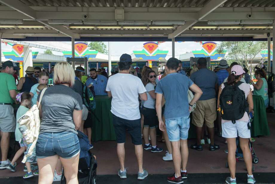 """Visitors wait to go through security at Walt Disney World Resort Magic Kingdom in Orlando, Florida, on September 12, 2017 two days after Hurricane Irma hit Florida. The resort reopened its doors Tuesday, welcoming locals and tourists who remain without power and air conditioning after Irma battered Florida. """"We are here because we are without power in Melbourne, Florida, and so we decided if we're going to bake, we might as well do it at Disney,"""" Veann Grigajtis, who travelled to Orlando with her family, told AFP.  / AFP PHOTO / NICHOLAS KAMMNICHOLAS KAMM/AFP/Getty Images Photo: NICHOLAS KAMM, Contributor / AFP or licensors"""