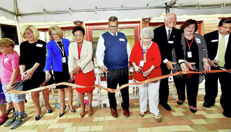 Cutting the ribbon Wednesday for the new Ronald McDonald House are, from left, Bennet Arnold, 7, of Ledyard; Cynthia Sparer, executive director of the Yale New Haven Children's Hospital; Marna Borgstrom, president/CEO Yale New Haven Health System; Scott Taylor, president of the Connecticut and Western Massachusetts McDonald's Owner Operators Association; Claire DiMartino of East Haven, founder of the Ronald McDonald House of CT; Stocky Clark, executive director of the Ronald McDonald House of CT; Ellen Good, president of RMH of CT Advisory Board; and Michael Favreau, president of RMHC-CTMA board of directors. Photo: Peter Hvizdak / Hearst Media Connecticut / New Haven Register