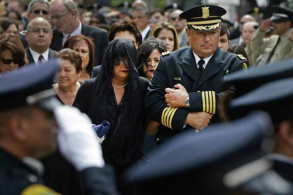 Cheryl Perez is escorted by Police Chief Art Acevedo from Wednesday's funeral service for her husband, Sgt. Steve Perez.
