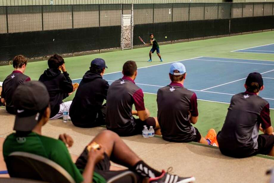 Tennis players from University of Detroit Jesuit watch as Dow High School sophomore Anish Middha plays an opponent from University of Detroit Jesuit at No. 1 singles during a tournament Wednesday at the Greater Midland Tennis Center. See Sports, Page 1B, for more coverage. (Katy Kildee/kkildee@mdn.net)