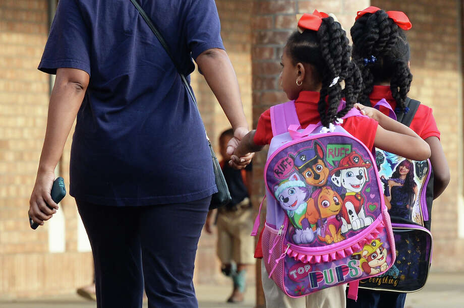 Dorian Riggs walks Kelsey Riggs, center, and Kayley Riggs to the first day of school at Guess Elementary on Wednesday. Photo taken Wednesday September 13, 2017  Guiseppe Barranco/The Enterprise Photo: Guiseppe Barranco, Photo Editor / Guiseppe Barranco ©