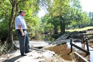 Idylwild Golf Club co-owner Ray Moore stands at the foot of a where the bridge on Hole No. 6 once stood at a point where Pine Island Bayou crosses into the course. Bridges on holes No. 4 and 5 were damaged in similar fashion when floodwaters rose during Tropical Storm Harvey. (Mike Tobias/The Enterprise)