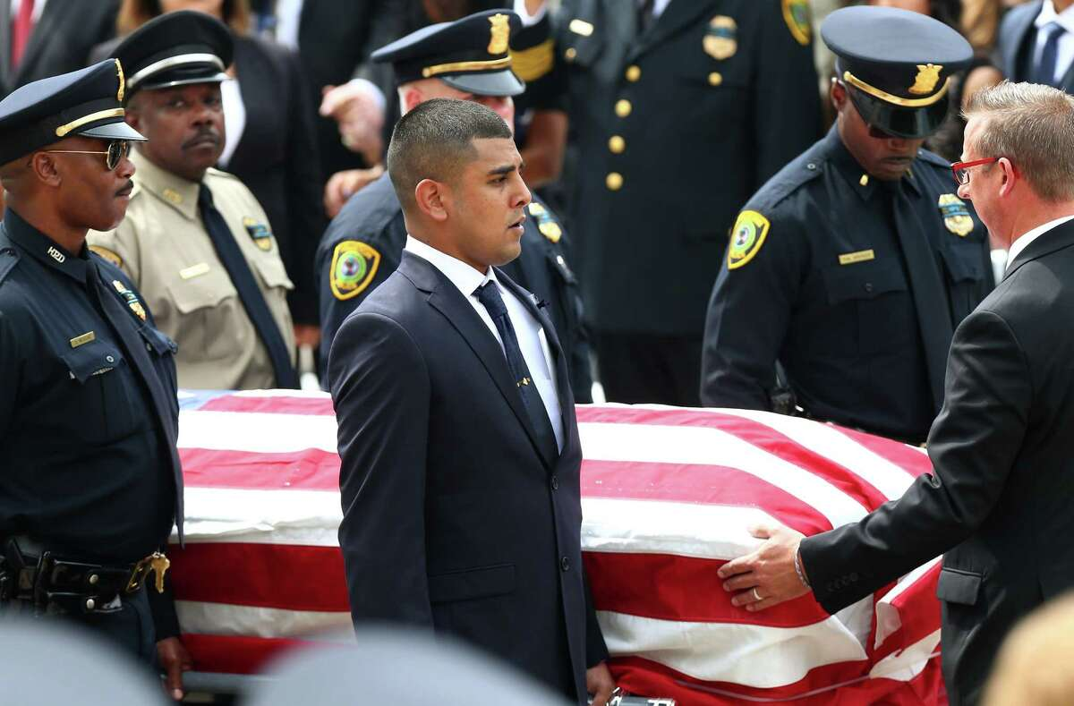 Maverick Perez, along with the other pallbearers, carries his father's coffin outside Co-Cathedral of the Sacred Heart church Wednesday, Sept. 13, 2017, in Houston. Perez's father, Houston Police Sgt. Steve Perez, 60, died in the line of duty while reporting for work during Hurricane Harvey.