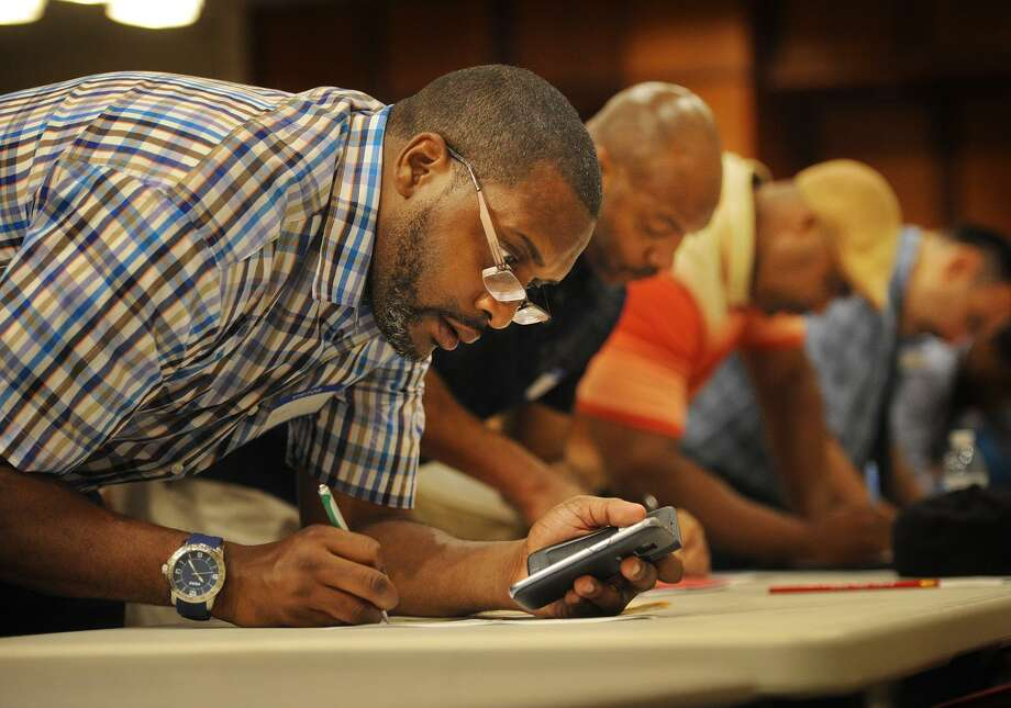 Sean Toliver, left, of Bridgeport, fills out a job application at a job fair for ex-offenders, the Bridgeport Re-Entry Career Fair, at the Margaret Morton Government Center in Bridgeport, Conn. on Wednesday, June 28, 2017. Photo: Brian A. Pounds / Hearst Connecticut Media / Connecticut Post