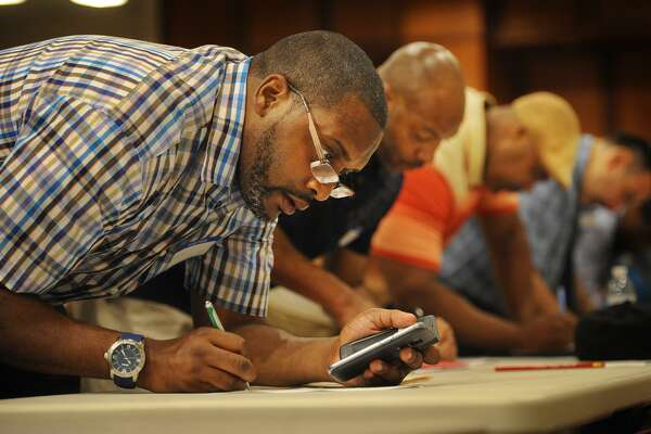 Sean Toliver, left, of Bridgeport, fills out a job application at a job fair for ex-offenders, the Bridgeport Re-Entry Career Fair, at the Margaret Morton Government Center in Bridgeport, Conn. on Wednesday, June 28, 2017.