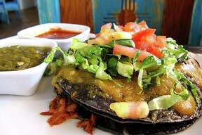 """Blue corn stacked enchiladas with pork adobado, lettuce, tomatoes and cheese with a """"Christmas"""" set of green and red chile sauces from Santa Fe Trail Mexican Cuisine on San Pedro Avenue."""
