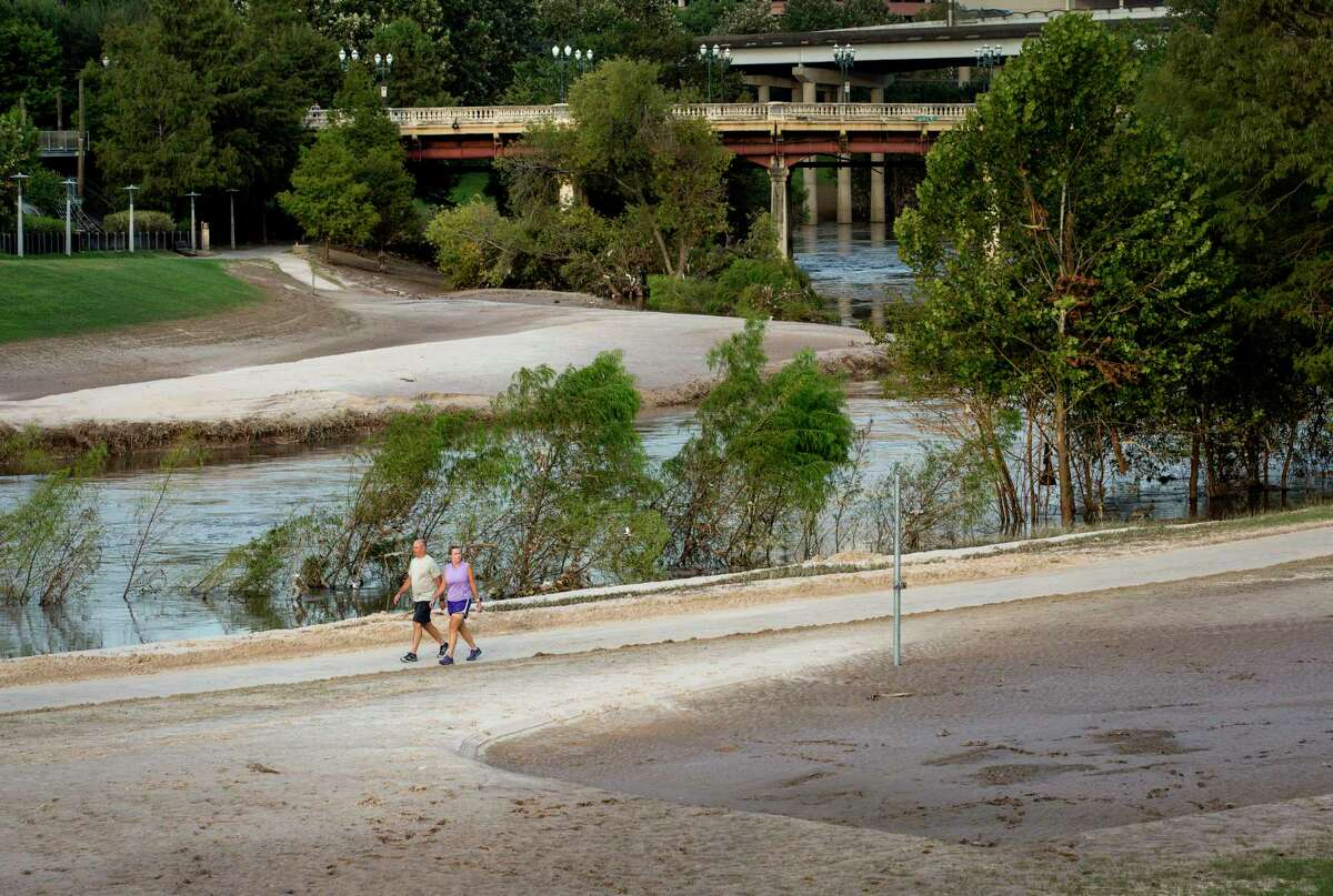 Two people walk along a trail at Buffalo Bayou Park, Tuesday, Sept. 12, 2017, in Houston. Floodwaters from Hurricane Harvey dumped silt over large areas of the park. ( Jon Shapley / Houston Chronicle )