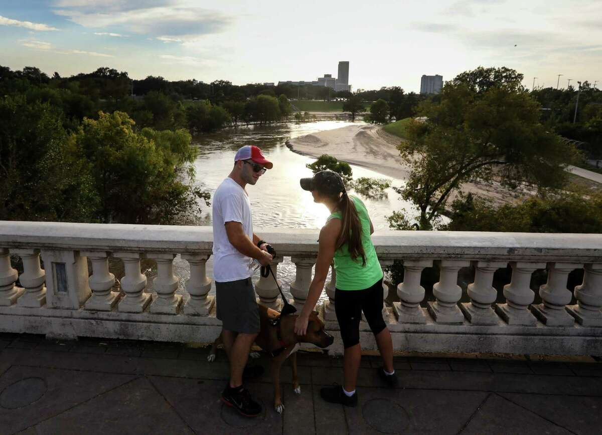 """Andrew Hoffmann, left, and his girlfriend Allison Hubert walk their dog at Buffalo Bayou Park, Tuesday, Sept. 12, 2017, in Houston. Floodwaters from Hurricane Harvey dumped silt over large areas of the park. """"It's kind of heartbreaking,"""" Hoffmann said. """"To see this and know it's going to be a very long time to get it back, it's just sad,"""" Hubert said. ( Jon Shapley / Houston Chronicle )"""