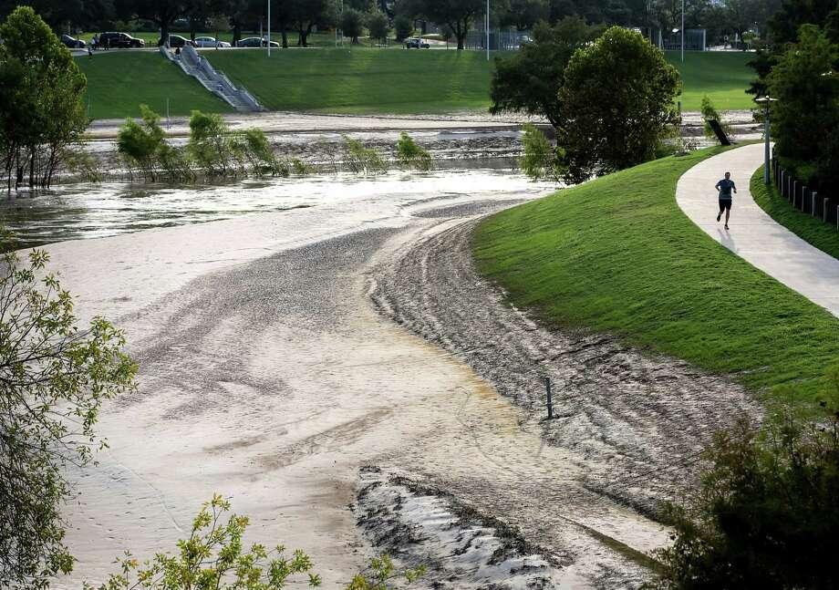 A jogger runs along a trail at Buffalo Bayou Park, Tuesday, Sept. 12, 2017, in Houston. Floodwaters from Hurricane Harvey dumped silt over large areas of the park.  ( Jon Shapley  / Houston Chronicle ) Photo: Jon Shapley, Staff / © 2017 Houston Chronicle