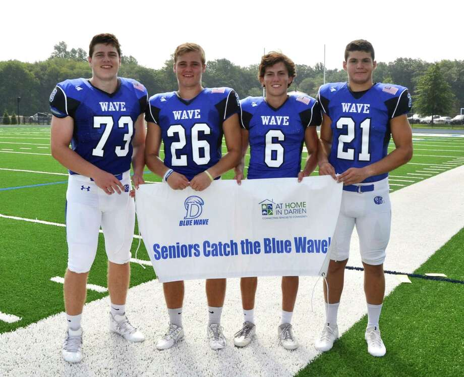 Darien High School football captains, from left, Michael Neary, Nick Green, Brian Minicus and Mitchell Pryor have extended an invitation to seniors to attend home games for free. Photo: Contributed / Contributed Photo