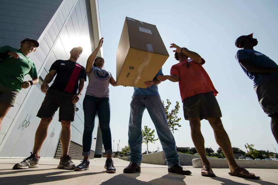 FILE - In Wednesday, Sept. 6, 2017, file photo, volunteers move boxes of shoes donated by Mythiquer Pickett for students affected by Hurricane Harvey on at the Delmar Field House in Houston. More than 50 local and national charities have raised more than $350 million in the nearly three weeks since Hurricane Harvey struck the Texas Gulf Coast. The disparate groups are now trying to decide on priorities while some storm victims wait for help. (AP Photo/Matt Rourke, File) Photo: Matt Rourke, STF / Copyright 2017 The Associated Press. All rights reserved.