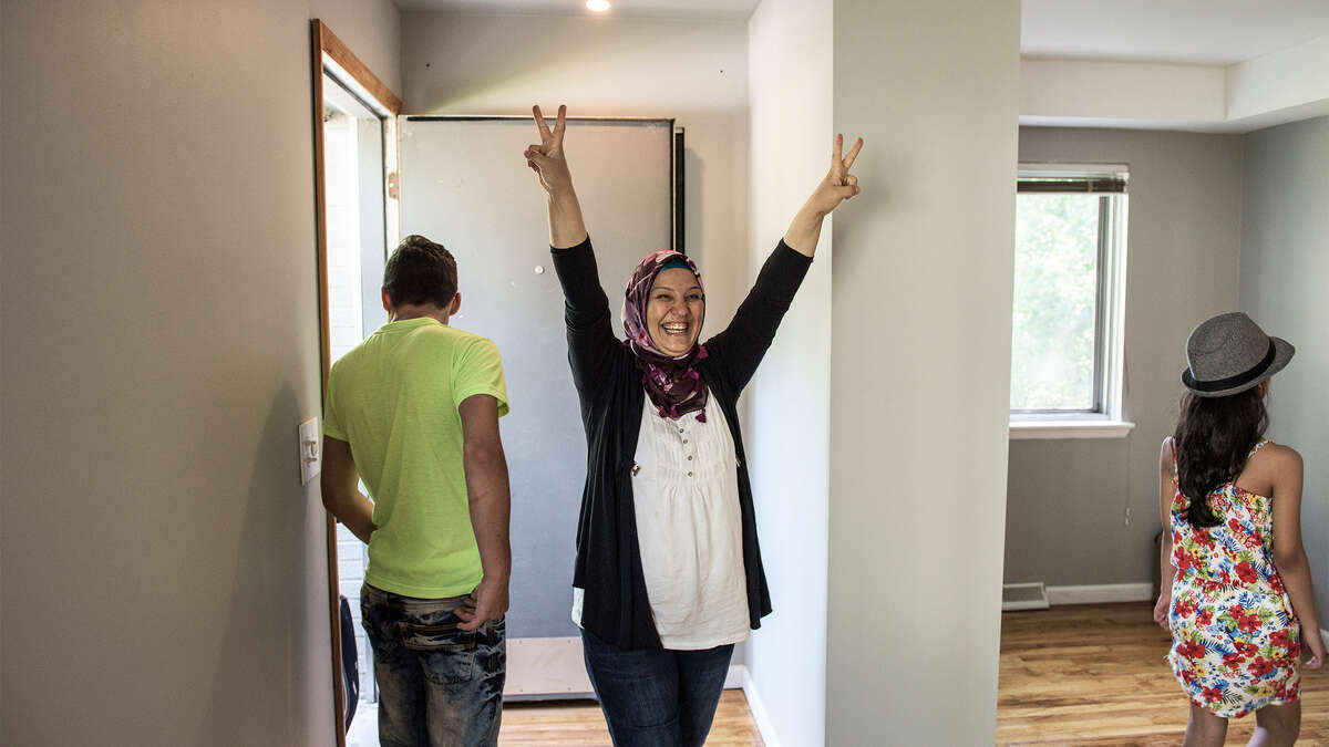 A Syrian refugee reacts after seeing her family's new home in Bloomfield Hills, MI