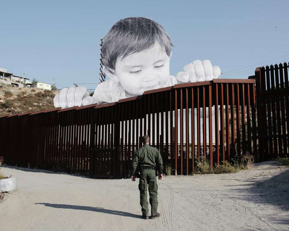 A border patrol officer on the U.S. side of the Mexico border wall, across from an art installation by artist JR, based on his photo of a 1-year-old visible from the California side near Tecate, Mexico. The art might be a metaphor for the future of the American workforce, which will be dependent on immigrants and their descendants. Photo: JOHN FRANCIS PETERS /NYT / NYTNS