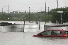 Cars submerged in parking lots on Louisiana Street as the Buffalo Bayou overflows into downtown Houston from Hurricane Harvey inches its way through the area on  Sunday, Aug. 27, 2017. ( Elizabeth Conley / Houston Chronicle )