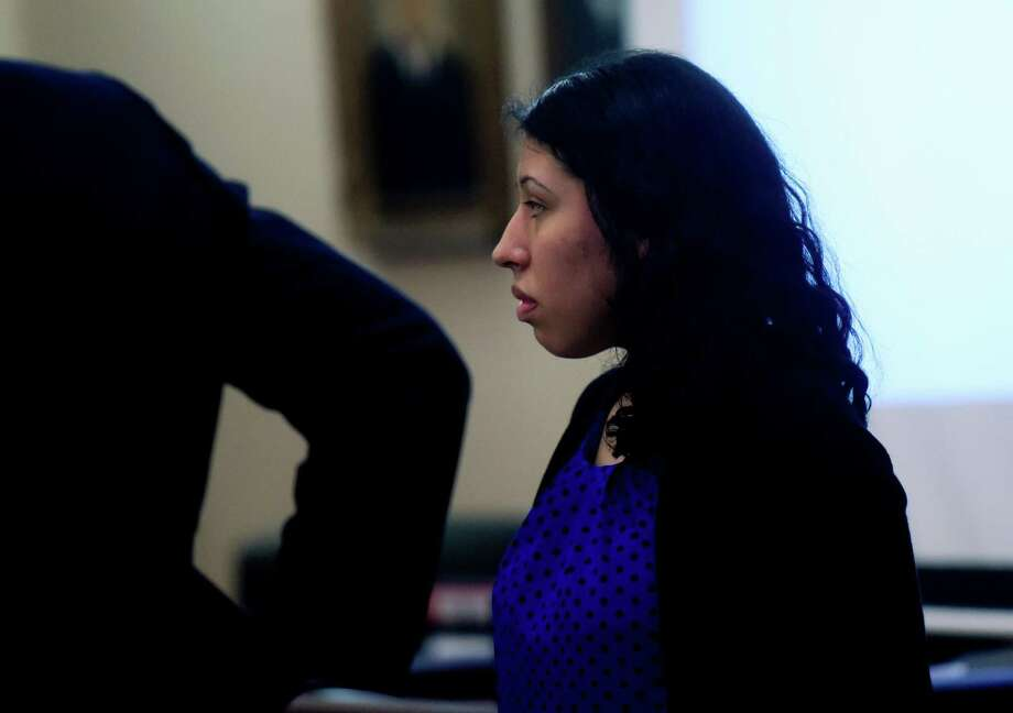 Antoinette Martinez, who is accused in the 2014 deaths of two men who were lured with the promise of sex to her apartment and then robbed and killed, stands in 175th District Court during opening statements Tuesday. Photo: Billy Calzada /San Antonio Express-News / San Antonio Express-News