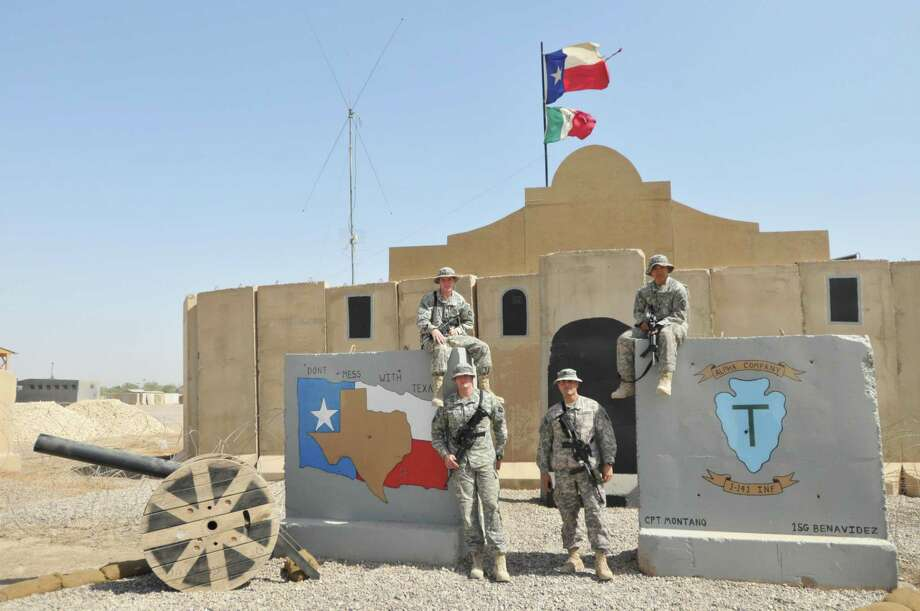 The photo shows four unnamed members of the 141st standing outside the Tactical Operations Center in Camp Liberty near Baghdad. Taken in 2010, the photo shows the building adorned with the iconic Alamo roofline made of painted plywood Photo: CourtesyTexas Military Forces Museum