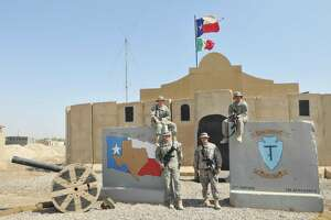 The photo shows four unnamed members of the 141st standing outside the Tactical Operations Center in Camp Liberty near Baghdad. Taken in 2010, the photo shows the building adorned with the iconic Alamo roofline made of painted plywood