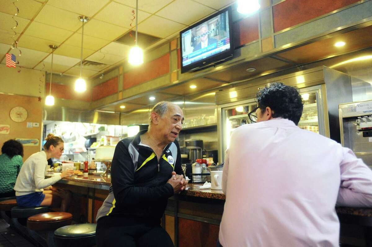 """Republican candidate for mayor Barry Michelson talks with Stamford resident Ronald Morse inside Bedford Street Diner about how he would improve transportration and pedestrian infrastructure before a """"Cycling with Candidates"""" event in downtown Stamford."""