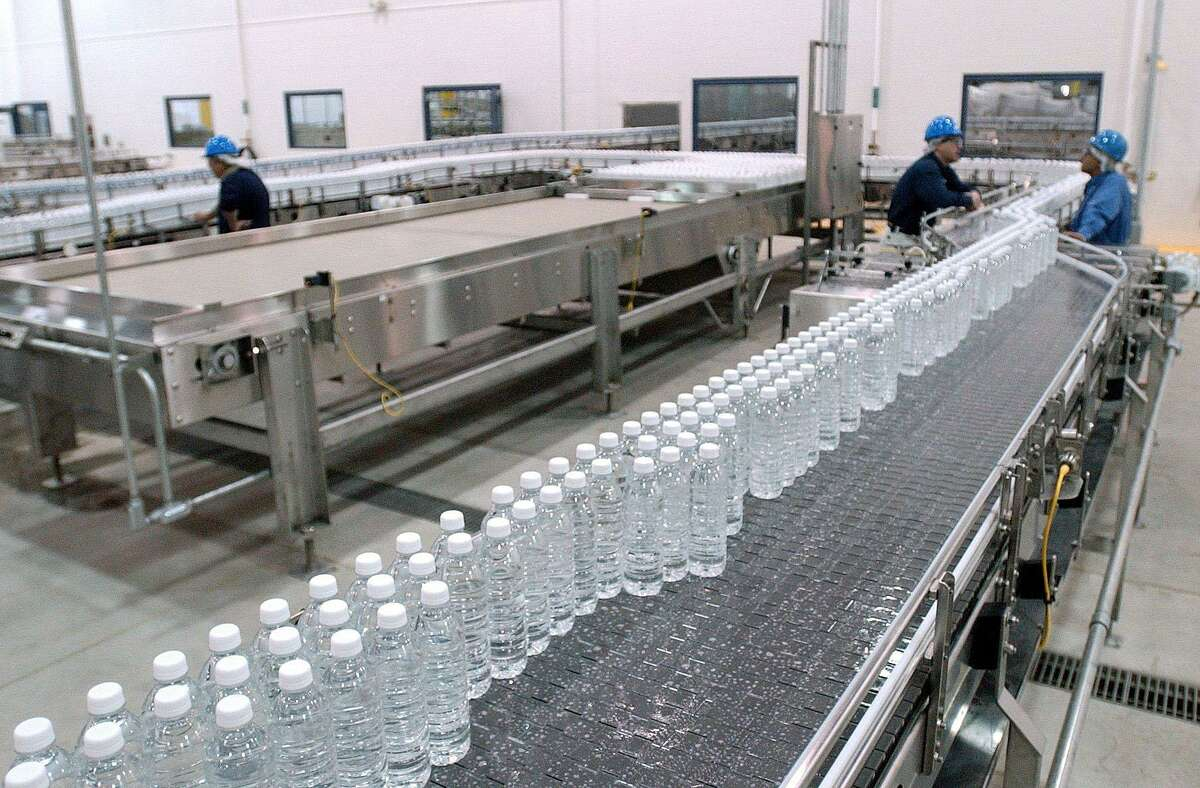 """A stream of bottles full of """"test product"""" move down a conveyor belt on the production floor of the Ice Mountain plant in Stanwood, Mich."""