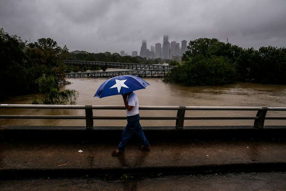 Armando Bustsamante walks along the street over Buffalo Bayou as flood waters from Tropical Storm Harvey flow toward downtown Houston Tuesday, Aug. 29, 2017.  More than 17,000 people are seeking refuge in Texas shelters, the American Red Cross said. With rescues continuing, that number seemed certain to grow. (Michael Ciaglo/Houston Chronicle via AP)Purchase your copy here. Photo: Michael Ciaglo/Houston Chronicle