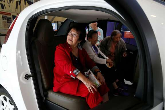 Kate Gong (left) and friends sit inside a Waymo self-driving car displayed at the Computer History Museum in Mountain View, Calif. on Wednesday, July 12, 2017.