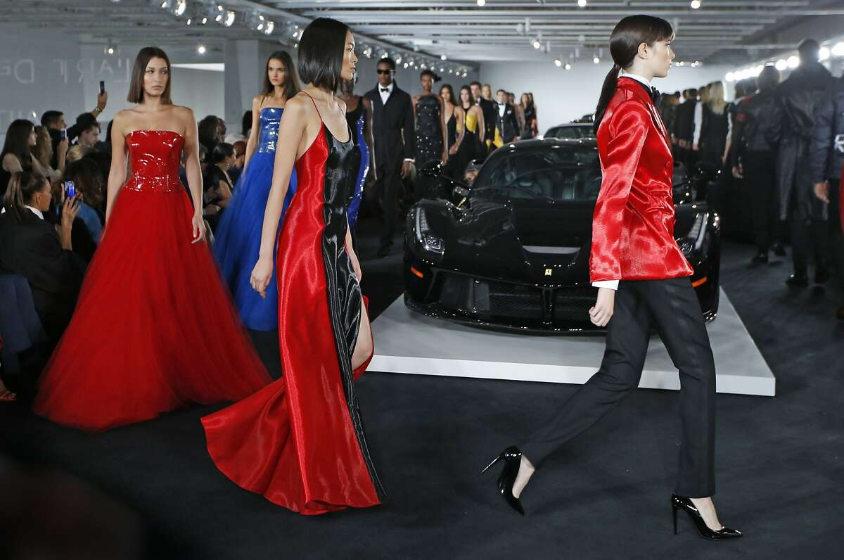 Models walk the runway in front of Ralph Lauren's car collection in The Garage at the Ralph Lauren fashion show during Fashion Week, Tuesday, Sept. 12, 2017, in Bedford, NY. (AP Photo/Kathy Willens)