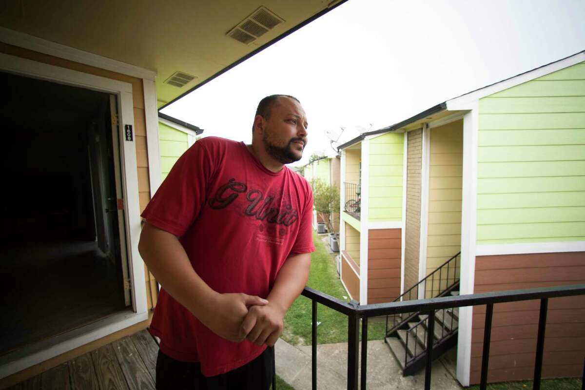 Steven Calhoun, 31, stands on the balcony of his apartment north of Houston, Wednesday, Sept. 13, 2017. Calhoun missed five days at his job packing airplane meals at George Bush Intercontinental Airport, and now is facing an eviction notice, on top of struggling to afford food. He's applied for FEMA aid and disaster unemployment insurance, but that takes weeks to process.