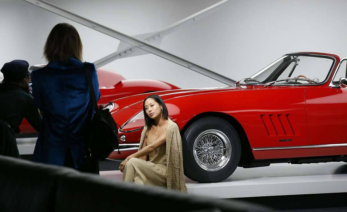 Guests take photographs of each other in front of Ralph Lauren's car collection in The Garage after the Ralph Lauren fashion show during Fashion Week, Tuesday, Sept. 12, 2017, in Bedford, NY. (AP Photo/Kathy Willens)