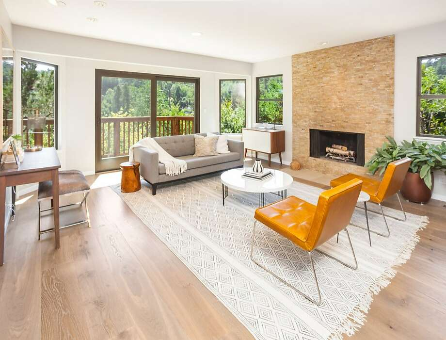 The living room at 403 Wendy Way in Mill Valley features a fireplace with a floor-to-ceiling surround. Photo: Jeff Warrin / Redgate Photography