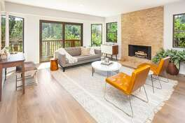 The living room features a fireplace with a floor-to-ceiling surround.