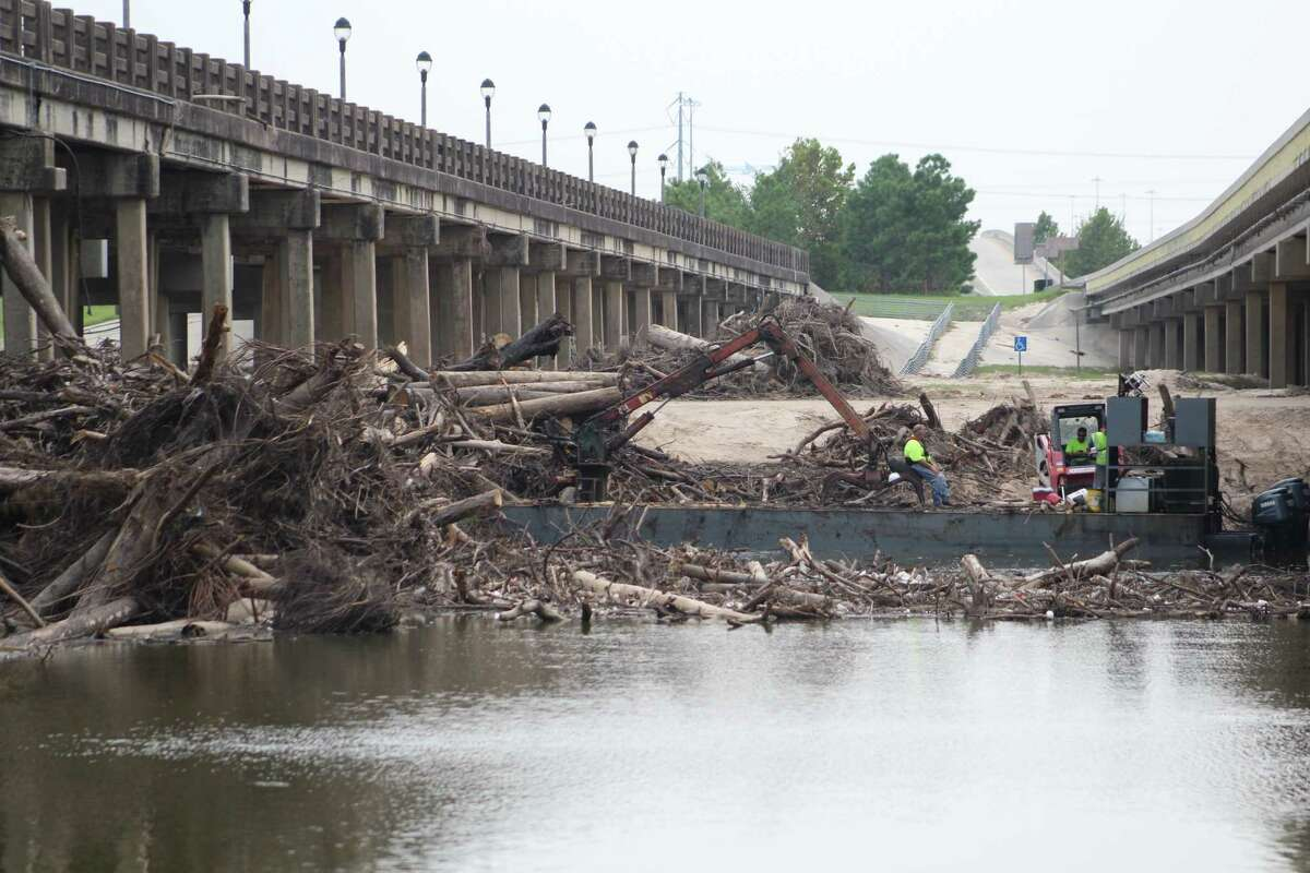 Tree branches litter the San Jacinto River between the northbound and southbound lanes of Interstate 69 near Kingwood.