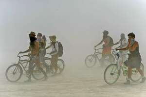 Burning Man participants walk their bikes during a dust storm at the annual Burning Man event on the Black Rock Desert of Gerlach, Nev., on Friday, Aug. 29, 2014. Organizers call Burning Man the largest outdoor arts festival in North America, with its drum circles, decorated art cars, guerrilla theatrics and colorful theme camps. (AP Photo/The Reno Gazette-Journal, Andy Barron)
