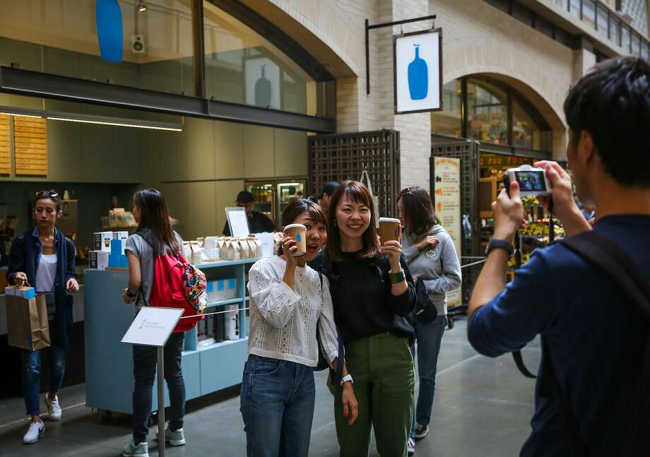 People pose for a photograph after getting a coffee outside of the Blue Bottle Coffee stand in the Ferry Building in San Francisco, Calif., on Thursday, Sept. 14, 2017. Photo: Gabrielle Lurie, The Chronicle