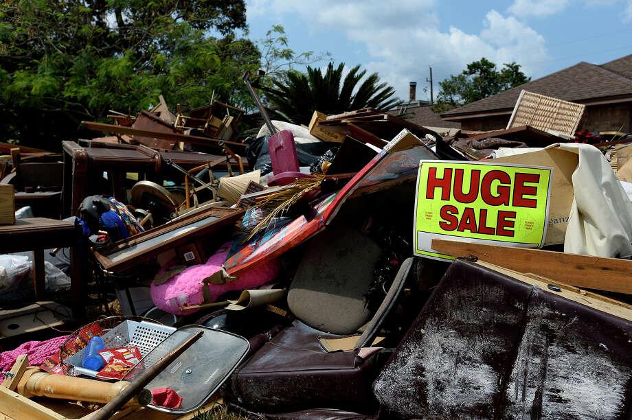 A sign advertises a yard sale on a pile of debris in Vidor's Wexford Park neighborhood on Thursday.  Photo taken Thursday 9/14/17 Ryan Pelham/The Enterprise Photo: Ryan Pelham / ©2017 The Beaumont Enterprise/Ryan Pelham