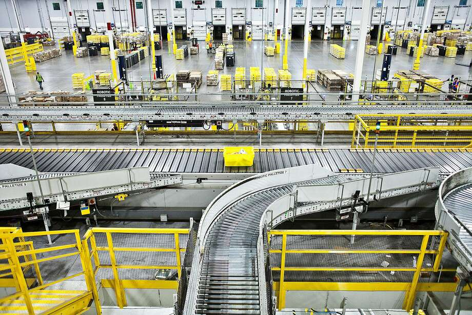 A bin moves along a conveyor belt at an Amazon warehouse in Florence, N.J. Amazon is on the forefront of automation, finding new ways of getting robots to do the work once handled by human employees. Photo: BRYAN ANSELM, NYT
