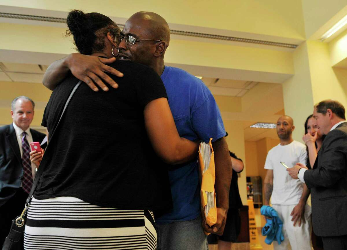 Carl Dukes hugs his cousin, Desiree Dukes, at the Albany County Judicial Center on Thursday, July 7, 2016, in Albany, N.Y. Dukes and Lavell Jones, background third from right, were imprisoned for the 1997 killing of Erik Mitchell, a University at Albany student. The murder conviction was overturned. (Paul Buckowski / Times Union archive)