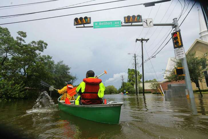 Houston firefighters use a borrowed canoe to search for evacuees during extreme flooding in Meyerland in the wake of Hurricane Harvey on  Aug. 27.  (Mark Mulligan / Houston Chronicle)