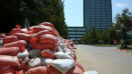 Sand bags that were used to dam the Westlake One Office Tower of BP headquarters, back, during Hurricane Harvey flood are now stacked at a staging area on BP campus Thursday, Sept. 14, 2017, in Houston. Thousands of sand bags were put around the Westlake One buildling and the low-rise office building next to it and a parking garage during the flood in order to prevent more water going into the buildings. ( Yi-Chin Lee / Houston Chronicle )