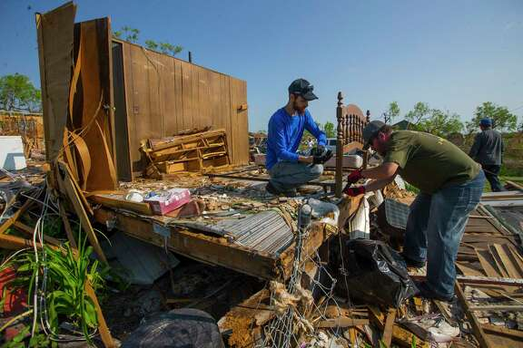 Volunteers from Abilene clean up what was the bedroom in the destroyed home of Eddie and Barbara De Luna.
