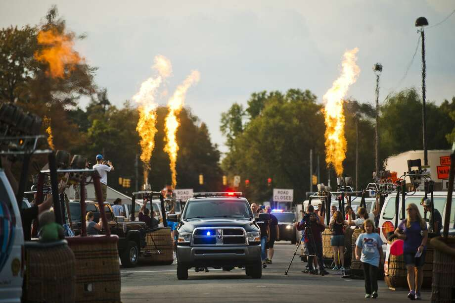 Hot air balloon pilots light their burners as walkers in the Law Enforcement Torch Run for Special Olympics Michigan begin to walk down Main Street during a hot air balloon burner glow as part of the Midland Balloon Festival on Thursday, September 14, 2017 on Main Street. (Katy Kildee/kkildee@mdn.net) Photo: (Katy Kildee/kkildee@mdn.net)