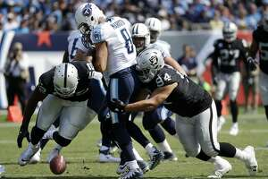 Oakland Raiders defensive end Khalil Mack (52) and defensive tackle Eddie Vanderdoes (94) chase after a fumble by Tennessee Titans quarterback Marcus Mariota (8) in the second half of an NFL football game Sunday, Sept. 10, 2017, in Nashville, Tenn. The Titans recovered the ball. (AP Photo/James Kenney)