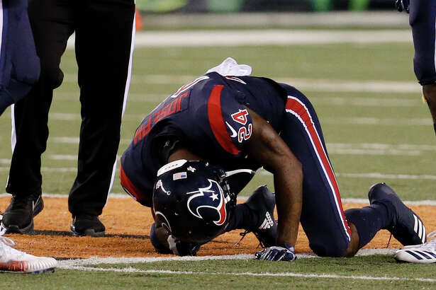 Houston Texans cornerback Johnathan Joseph (24) kneels on the field after an apparent injury in the first half of an NFL football game against the Cincinnati Bengals, Thursday, Sept. 14, 2017, in Cincinnati. (AP Photo/Frank Victores)