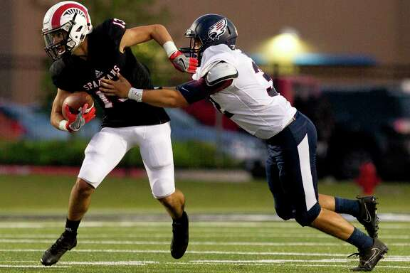 Porter wide receiver Tayler Baker (13) tries to get past Katy Tompkins linebacker Ryan Cillessen (32) during the first quarter of a non-district high school game against Katy Tompkins at Texan Drive Stadium, Thursday, in New Caney.
