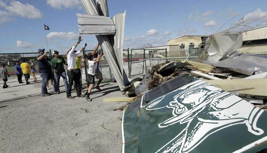 Volunteers at Rockport-Fulton High School clear debris from the stadium left by Hurricane Harvey. Photo: Eric Gay /Associated Press / Copyright 2017 The Associated Press. All rights reserved.
