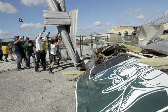 Volunteers at Rockport-Fulton High School clear debris from the stadium left by Hurricane Harvey.