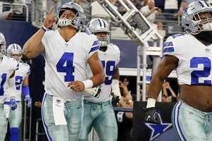 Dallas Cowboys' Dak Prescott (4) and Ezekiel Elliott (21) lead the team onto the field for a preseason NFL football game against the Oakland Raiders on Saturday, Aug. 26, 2017, in Arlington, Texas. (AP Photo/Roger Steinman)